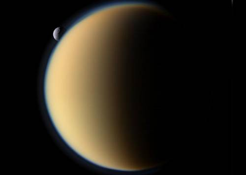 Saturn's Moon Titan's Hazy Atmosphere With Tethys In The Background